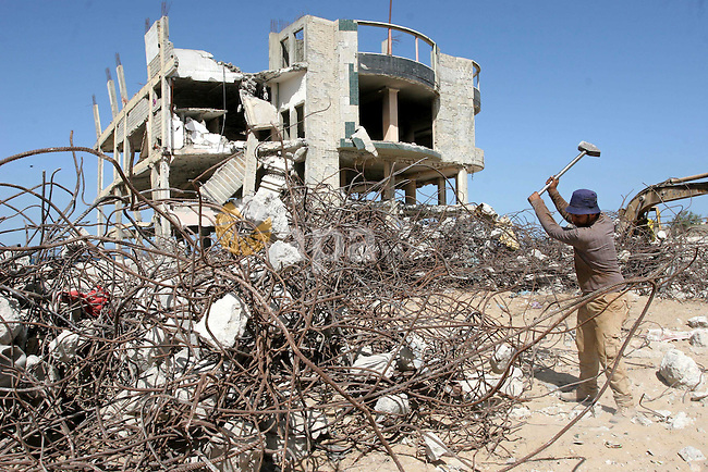A Palestinian worker extracts iron from the rubbles of Shihab Balas hotel and Al-Jazeera hotel which destroyed during Israel's 22-days military assault over Gaza Strip , in Gaza City on Oct. 13,2010. These iron are used to rebuild a new houses because Israel prevents entering the iron into the Gaza Strip . Photo by Mohammed Asad