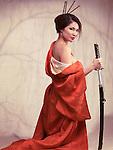 Beautiful sexy asian woman in red kimono unsheathing katana sword