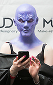 London, UK. 12 April 2015. A model at Make-up designory has a quick look at her mobile phone. United Makeup Artists Expo (UMAe), the UK's leading aspiring and professional hair and makeup artist trade show, at the Business Design Centre in Islington, London, UK. It runs until Sunday, 12 April. At this trade show leading professionals provide demonstrations and the latest techniques and products are showcased.
