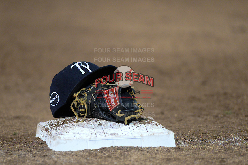 Tampa Yankees hat on top of a Rawlings glove in between innings during a game against the Fort Myers Miracle on April 15, 2015 at Hammond Stadium in Fort Myers, Florida.  Tampa defeated Fort Myers 3-1 in eleven innings.  (Mike Janes/Four Seam Images)