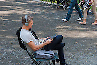 A parkgoer uses his iPad to listen to music in Bryant Park in New York on Tuesday, July 24, 2012 (© Richard B. Levine)