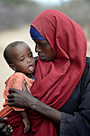 Carrying one of her children, a woman pauses to rest while trekking across eastern Kenya near the Somali border. The Somali woman left her home a month earlier, fleeing drought and conflict, to head for the Dadaab refugee complex. Already the world's world's largest refugee settlement, Dadaab has swelled in recent weeks with tens of thousands of recent arrivals from Somalia.