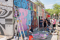 Rubin415 and other street artists at work at the Welling Court Mural Project in the Astoria neighborhood of Queens in New York on Saturday, June 13, 2015. The annual neighborhood event decorates walls in this industrial part of Astoria. The project is crowd-funded and emerging street artists work side by side with established stars.  (© Richard B. Levine)