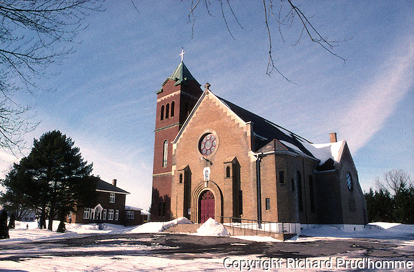 Catholic Church in Notre-Dame-des-Lourdes in winter, side view.  Red brick church