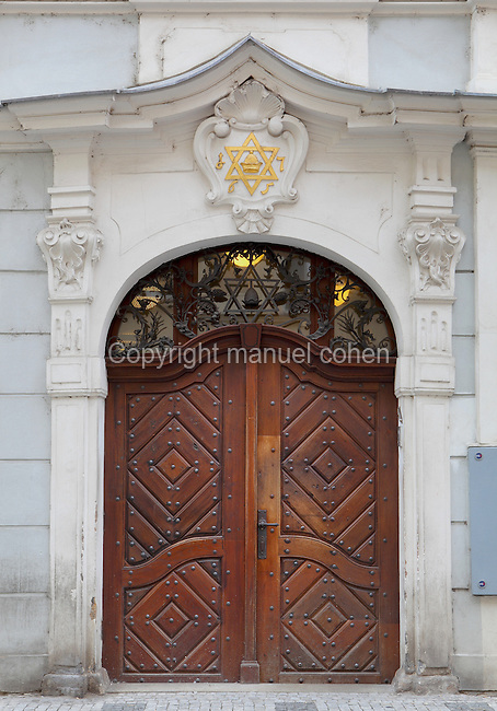 Entrance of the Chief Rabbinate on the Jewish Town Hall or zidovska radnice, built next to the Old New Synagogue on the corner of Maiselova and Cervena Ulice in 1586 in Renaissance style under the sponsorship of Mayor Mordechai Maisel, with a Rococo facade added in the 18th century, in the Josefov or Jewish quarter of Prague, Czech Republic. The studded wooden doors are topped with 2 stars of David, in iron on the window fretwork and gold on the stone decorative pediment. The historic centre of Prague was declared a UNESCO World Heritage Site in 1992. Picture by Manuel Cohen