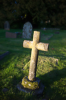 Religious cross marks grave in graveyard at Northleach in Gloucestershire in The Cotswolds, UK