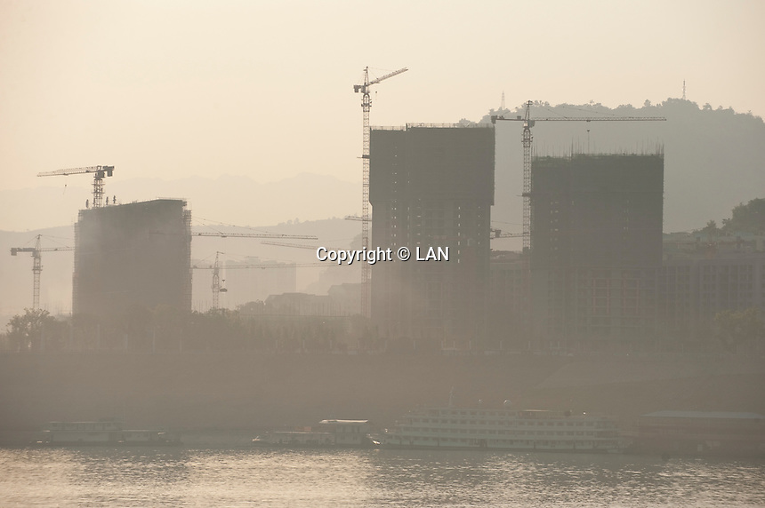 Daytime landscape view of the Cháng Jiāng with commercial buildings under construction in the background at the Tiancheng migration development area in the Wànzhōu District in the Chongqing Municipality.  © LAN