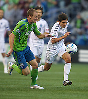 Seattle Sounders FC defender Tyson Wahl, left, and Vancouver Whitecaps FC  midfielder Shea Salinas race to the ball during play at Qwest Field in Seattle Saturday June 11, 2011. The game ended in a 2-2 draw.