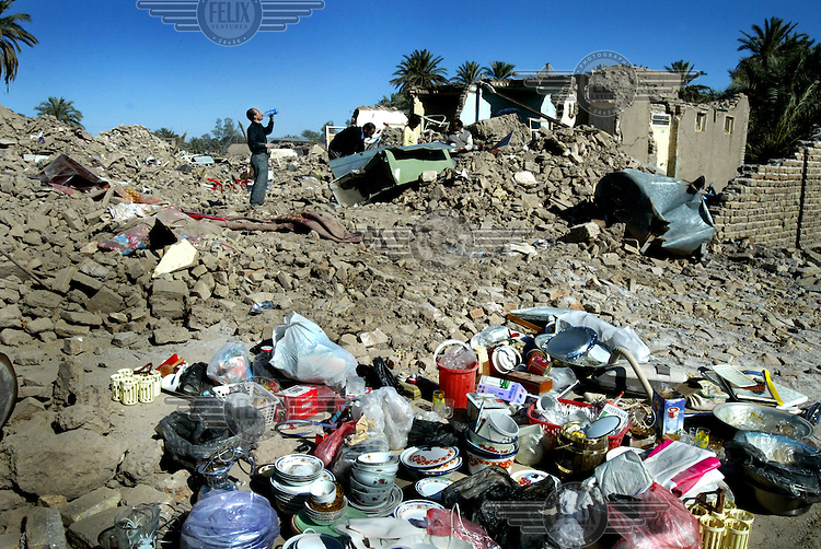 Survivors of the Bam earthquake search the rubble of their homes for possessions..An earthquake measuring 6.3 on the Richter scale caused widespread devastation in the ancient city of Bam and other parts of Kerman Province, leaving at least 30,000 people dead.