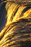 Canada, Ontario, Niagara Falls, close-up of waterfalls with golden sunlight  highlighting the water