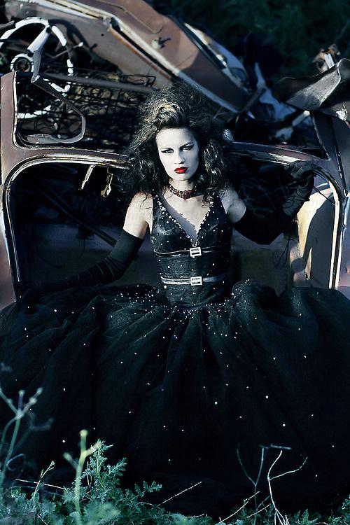 A girl in a black dress sitting in a rusted car trunk