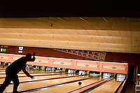 "Silhouette of man bowling at ""Lanes and Games."""