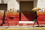 Mulher se protege do sol com guarda-chuva, município de Foresta, Pernambuco, Brasil.