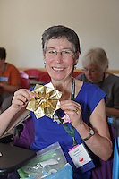 OrigamiUSA 2016 Convention at St. John's University, Queens, New York, USA. Creasers in Sunil Dhavalikar's Dahlia class. Louise Oppenheimer Flax, Connecticut, shows her completed model.
