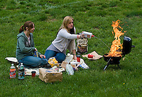 A woman sprays  starter fluid on lit charcoal as she and a friend prepare a barbecue at a city park. Photo Copyright Gary Gardiner. Not be used without written permission detailing exact usage.
