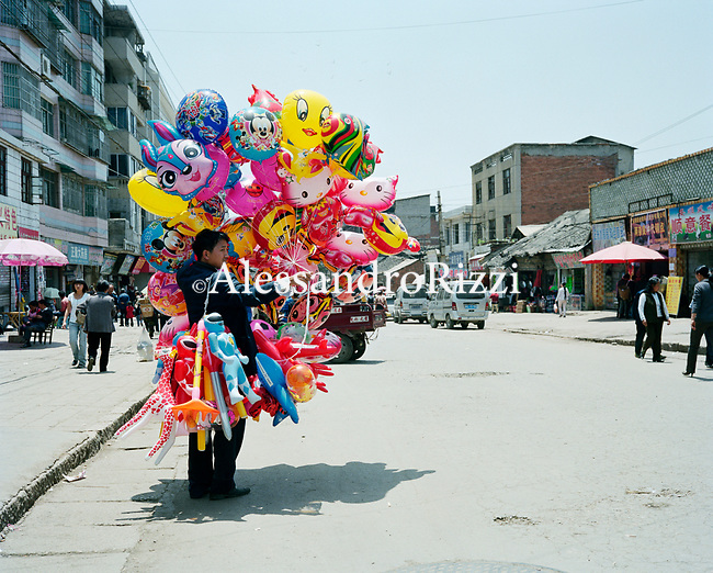 Man selling balloons and toys along a street