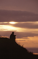 26 JUN 2002 - KHOVSGOL NATIONAL PARK, MONGOLIA -  A Mongolian horseman sits at the top of Chichee Pass watching the sunrise. (PHOTO (C) NIGEL FARROW)