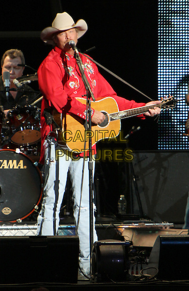ALAN JACKSON.recently made a stop on his tour at the Verizon Wireless Amphitheater, Alpharetta, GA, USA, .April 10th 2010..country music concert gig live on stage .half 3/4 length red shirt cowboy hat playing guitar jeans microphone singing .CAP/ADM/DH.©Dan Harr/AdMedia/Capital Pictures.