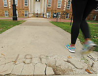 NWA Democrat-Gazette/ANDY SHUPE<br /> A student walks Friday, Aug. 21, 2015, past a damaged section of the 1906 portion of the Senior Walk on the east side of Old Main on the University of Arkansas campus in Fayetteville. University officials are considering a course of action to repair or replace the damaged sections.