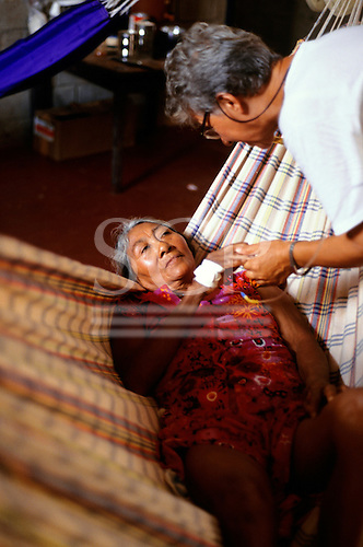 Boa Vista, Brazil. FUNAI doctor comforts a Yanomami Indian malaria victim lying in a hammock.