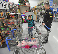 NWA Media/Michael Woods --12/06/2014-- w @NWAMICHAELW...Detective Bryan Lindabury with the Fayetteville Police Department helps Hali Smart, age 6 from Fayetteville, pick out a toy Saturday morning during the shop with a cop event at Walmart on MLK Blvd in Fayetteville.  Several local law enforcement agencies participating in the annual event to help local children, the Fayetteville police department help out about 100 local children during the event.