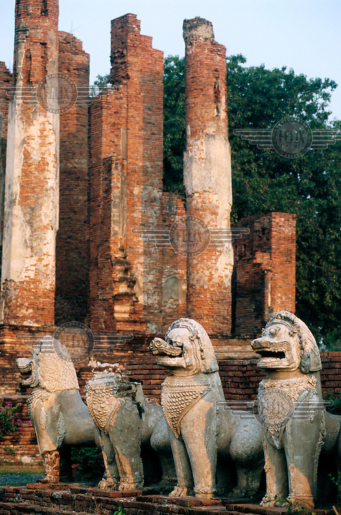 Wat Thammikarat temple ruins. The dilapidated remains of a large, early Ayutthayan, octagonal chedi surrounded by stucco and brick lions, or singhas. Ayutthaya was the most powerful kingdom in Siam in the mid-14th century. Its end came after years of conflict, when the capital was sacked by the Burmese in 1767. Today, Ayutthaya Historical Park is a UNESCO World Heritage Site.
