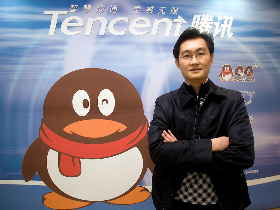 CEO of Tencent Holding Ltd Ma Huateng poses next to the company logo in the headquarters in Shenzhen, China January 18, 2007. To match story by David Barboza. Photo by Natalie Behring for the New York Times.