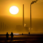 Climate change: Source of solar energy setting behind user of fossil fuel energy - sun setting behind Poolbeg Generating station, Ringsend Dublin, The Walkers are on Bull Island, in North Dublin. The energy generating power station is Ireland's second most polluting installation in terms of carbon dioxide, co2 emissions, according to the European Environment Agency. <br /> <br /> This image was &quot;Highly Commended&quot; in the &quot;Changing Climates&quot; category at the 2009 Environmental Photographer of the Year competition.