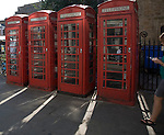 Four old red telephone boxes in the street, Cambridge, England woman walking into frame using a mobile phone.