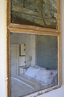 The double bed in a guest bedroom is reflected in an antique gilt-framed mirror inset with a hunting scene