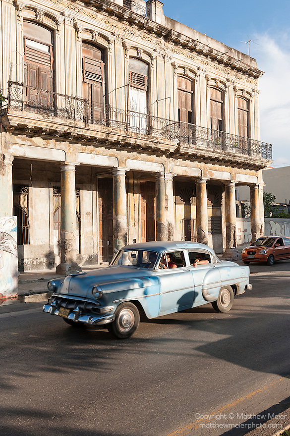 Havana, Cuba; a blue classic 1954 Chevy Bel Air driving down the Paseo de Marti in late afternoon sunlight