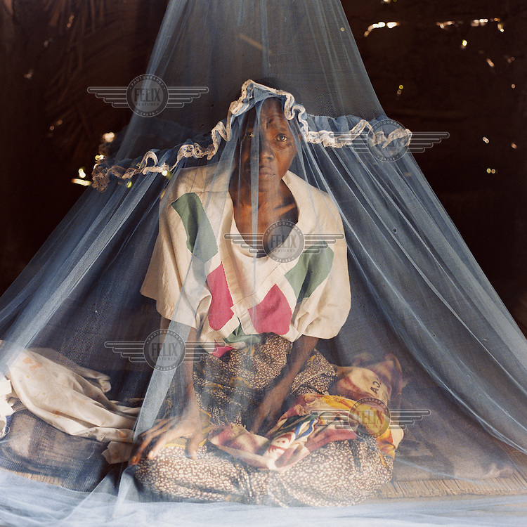 37 year old Casilda sits under a mosquito net at her home. She is HIV positive, and has been very sick over the last three months. Her husband and sons have been working to help her buy the necessary ARVT (Antiretroviral Therapy) drugs....