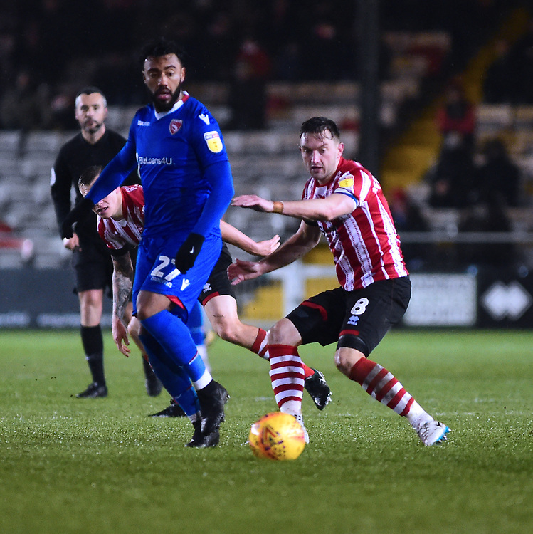 Lincoln City's Lee Frecklington, vies for possession with Morecambe's Jordan Cranston<br /> <br /> Photographer Andrew Vaughan/CameraSport<br /> <br /> The EFL Sky Bet League Two - Saturday 15th December 2018 - Lincoln City v Morecambe - Sincil Bank - Lincoln<br /> <br /> World Copyright © 2018 CameraSport. All rights reserved. 43 Linden Ave. Countesthorpe. Leicester. England. LE8 5PG - Tel: +44 (0) 116 277 4147 - admin@camerasport.com - www.camerasport.com