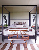 In the master bedroom, a four-poster bed by Hickory Chair is dressed in Restoration Hardware linens; the curtains are of a Ralph Lauren Home fabric, and the artwork is by Robert Longo.