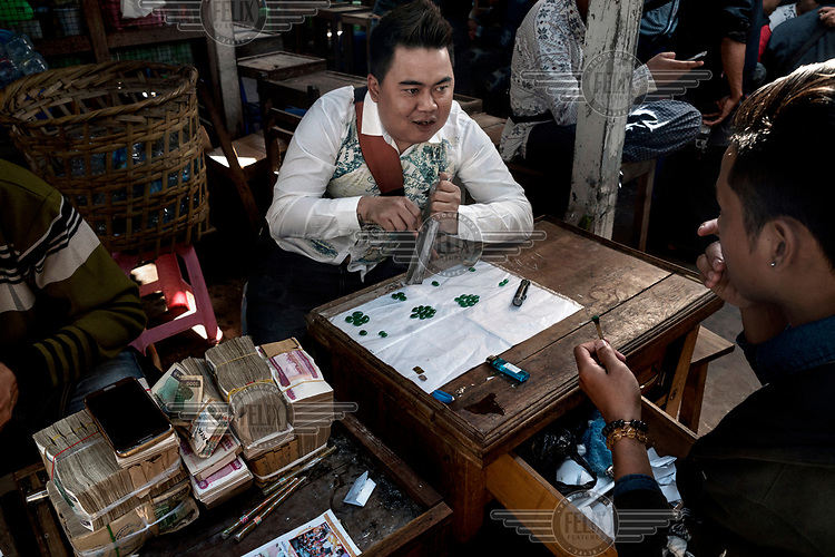 A jade seller (centre), sitting beside a huge pile of Kyat notes, polishes jade stones as he talks with a buyer (right) in the Mandalay Jade Market.