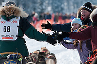 Musher # 68 Jeff Holt gets some high-fives from race fans at the Restart of the 2009 Iditarod in Willow Alaska