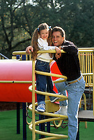 A smiling young girl and her father play on playground equipment.