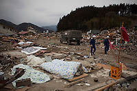 Rescue workers walk past bodies wrapped in blankets. Thousands of people died in this small town which ran out of body bags. On 11 March 2011 a magnitude 9 earthquake struck 130 km off the coast of Northern Japan causing a massive Tsunami that swept across the coast of Northern Honshu. The earthquake and tsunami caused extensive damage and loss of life.