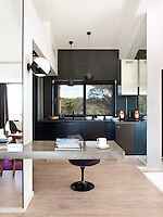 Black pendant lights by Tom Dixon, a Saarinen Tulip chair in the kitchen with matt black lacquered units
