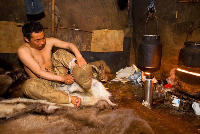 Inside the Polog (inner tent) of his Yaranga, Chukchi reindeer herder, Grisha Rahtyn, dresses entirely in traditional reindeer skin clothing. Chukotskiy Peninsula, Chukotka, Siberia, Russia