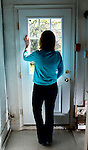 NOT MODEL RELEASED; FOR EDITORIAL USE ONLY...  solitary woman seen from behind looking out door of house