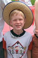 Smiling boy age 7 wearing straw hat Grand Old Day Parade.  St Paul  Minnesota USA