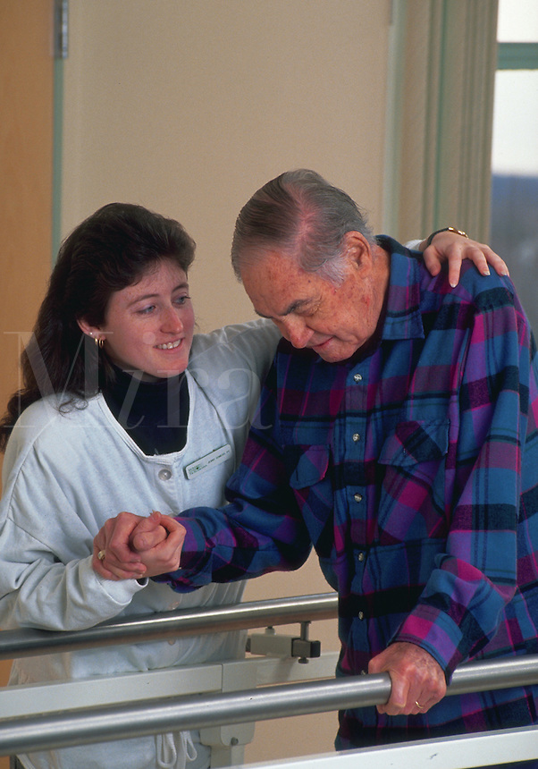 A senior male patient receives physical therapy at a rehabilitation hospital.