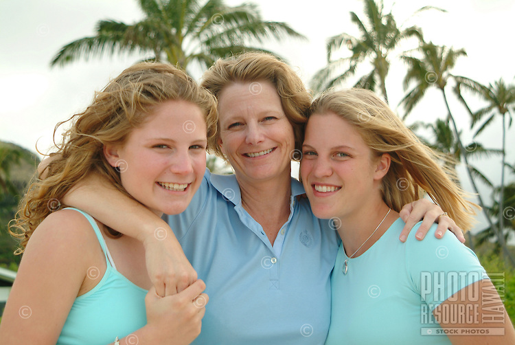 Portrait of two daughters and mother near palm trees