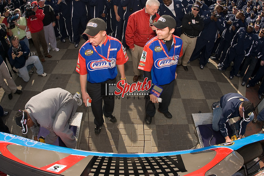 Wake Forest Demon Deacons assistant coach Keith Henry (left) squares off with Connecticut Huskies head coach Randy Edsall in a tire changing competition at Lowe's Motor Speedway Thursday, December 27, 2007 in Concord, NC.