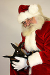 Santa Claus holding a black bunny rabbit in a cowboy hat