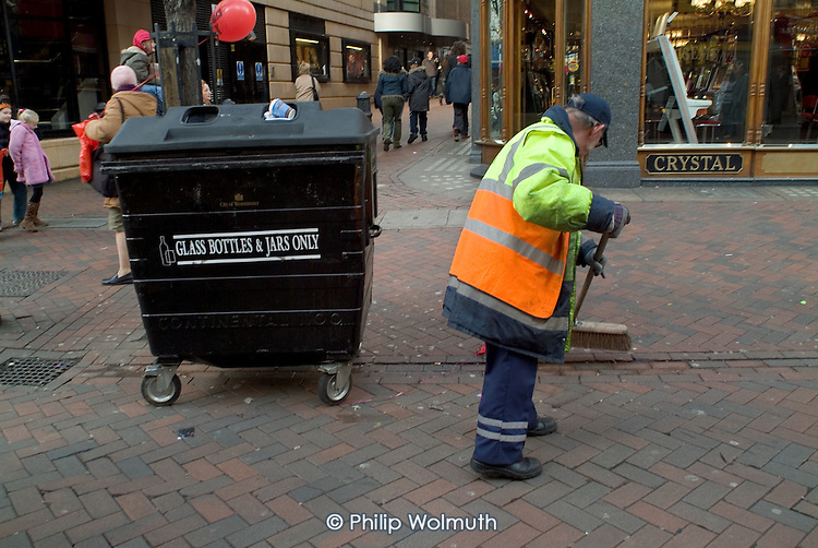 A street cleaner employed by private contractor Onyx sweeps up in Leicester Square, London.