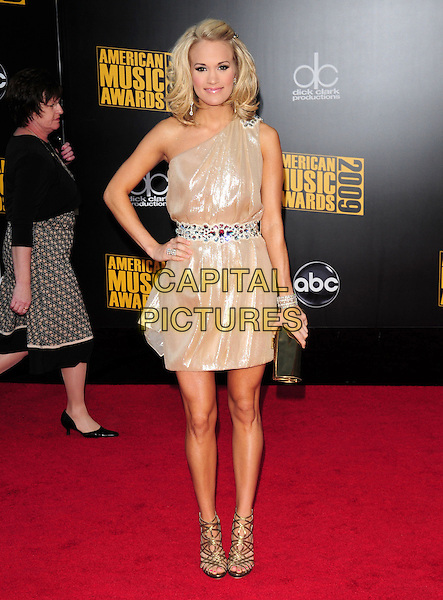 CARRIE UNDERWOOD.The 2009 American Music Awards held at The Nokia Theatre L.A. Live in Los Angeles, California, USA. .November 22nd, 2009.AMA AMA's full length dress one shoulder hand on hip silver gold embellished jewel encrusted belt clutch bag sandals .CAP/RKE.©DVS/RockinExposures/Capital Pictures