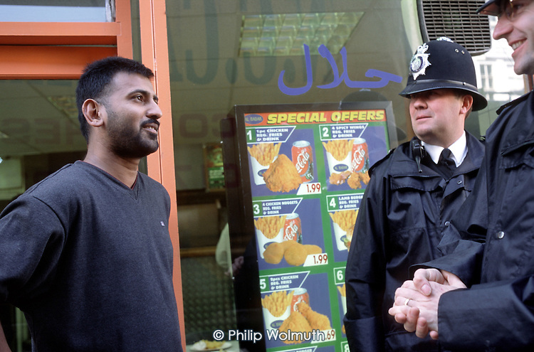 Sergeant Simpson and a colleague from the Brick Lane police office talk with a local resident while on patrol in Whitechapel, London.