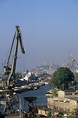 Bratislava, Slovakia. Bratislava port, with boats and cranes, and Bratislava Castle in the background.